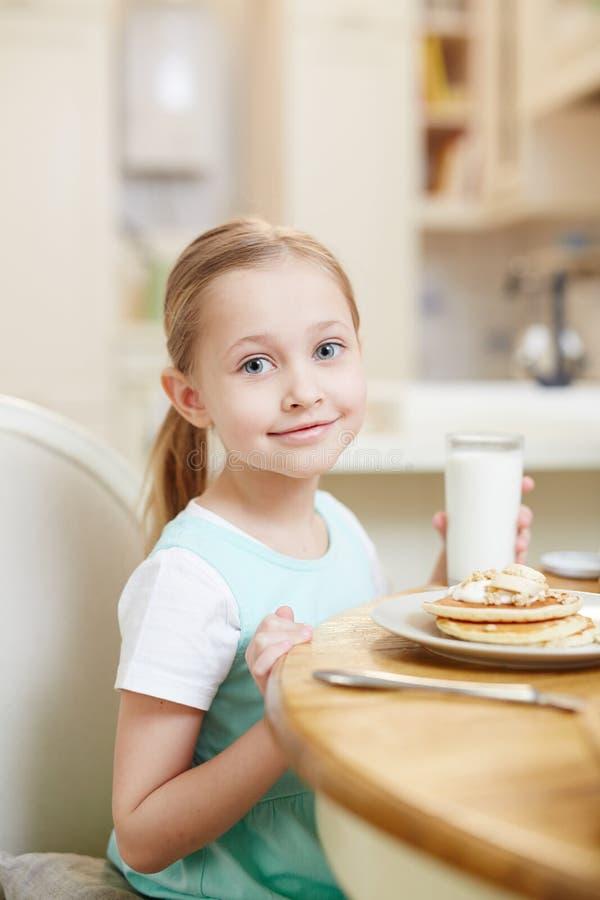 Leuke meisjesconsumptiemelk met pannekoeken royalty-vrije stock fotografie