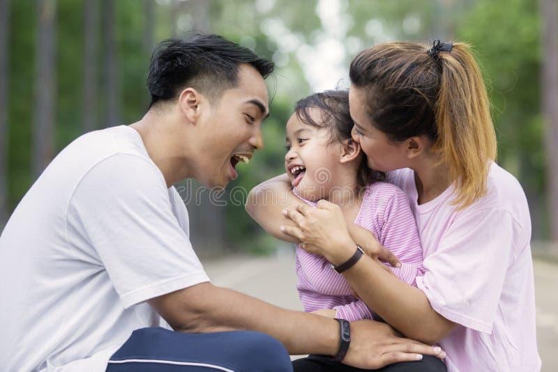 Leuke meisjespelen met haar ouders bij in openlucht royalty-vrije stock fotografie
