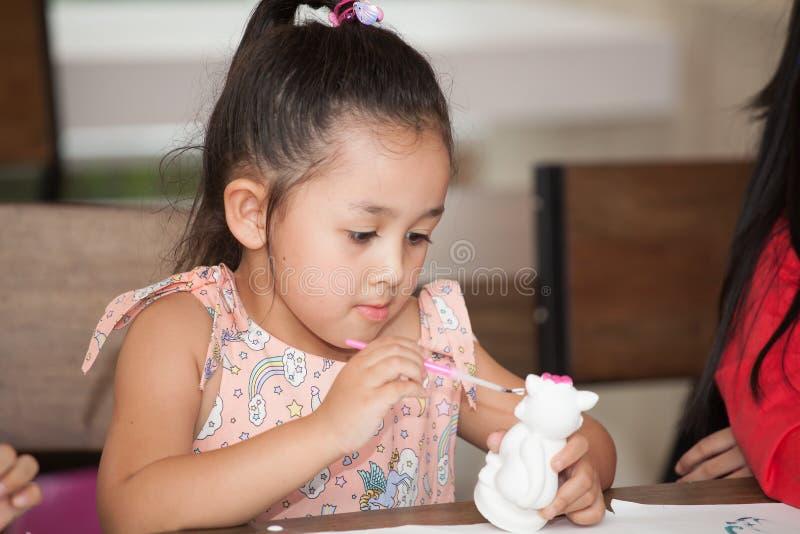 Leuke meisjestudent die een ceramisch aardewerkmodel in klaslokaalschool schilderen Jong geitjekunstenaar kindzitting bij bureauk royalty-vrije stock afbeeldingen