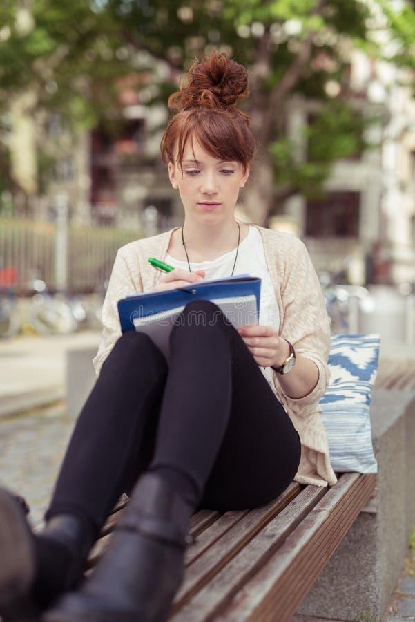 Leuke Meisjeszitting op Bank die op haar Nota's schrijven stock afbeeldingen