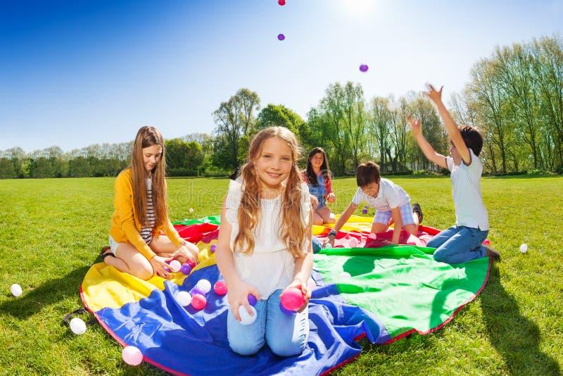 Leuke meisjeszitting op valscherm met kleurrijke ballen stock fotografie