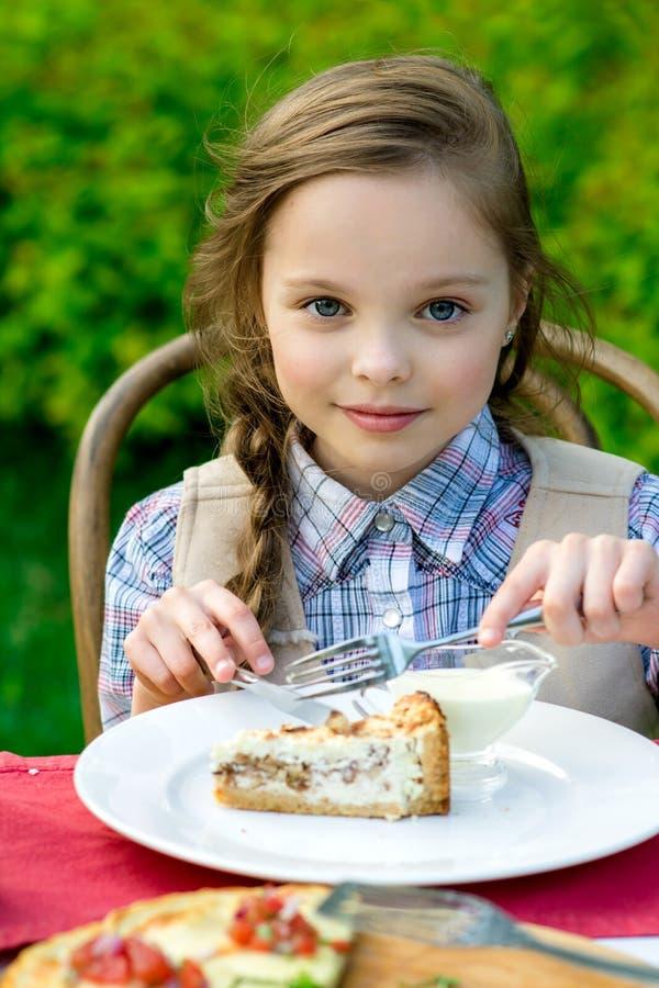 Leuke meisjezitting door dinerlijst en het eten stock foto's