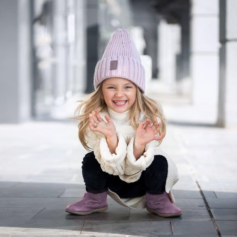 Leuke meisjezitting en lach in gebreide hoed stock fotografie
