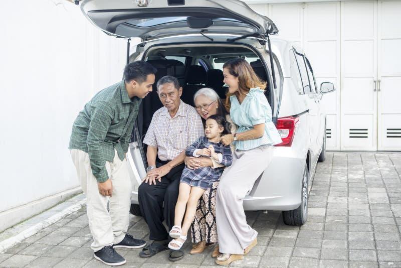 Leuke meisjezitting met haar familie in autoboomstam royalty-vrije stock foto's