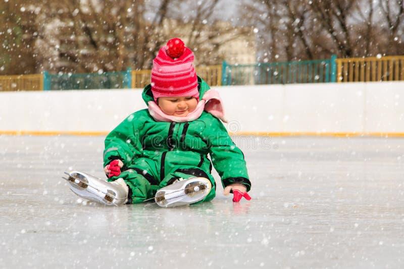 Leuke meisjezitting op ijs met vleten stock fotografie