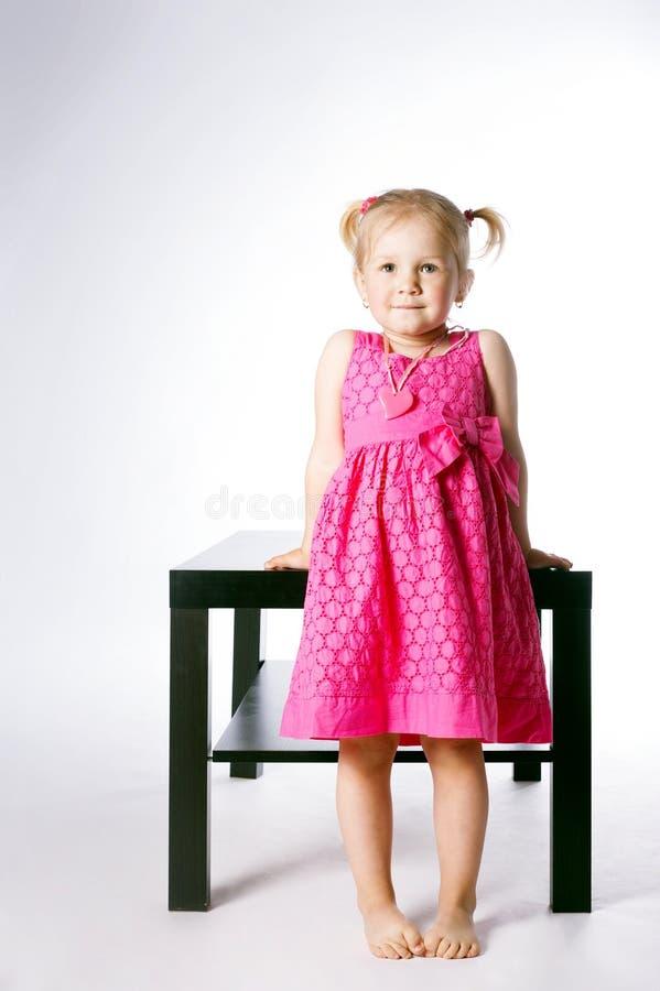 Leuke meisjezitting op lijst stock fotografie