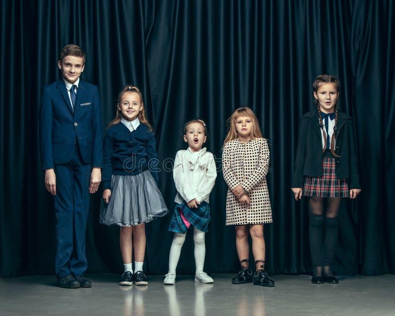 Leuke modieuze kinderen op donkere studioachtergrond De mooie tienermeisjes en de jongen die zich verenigen stock foto's