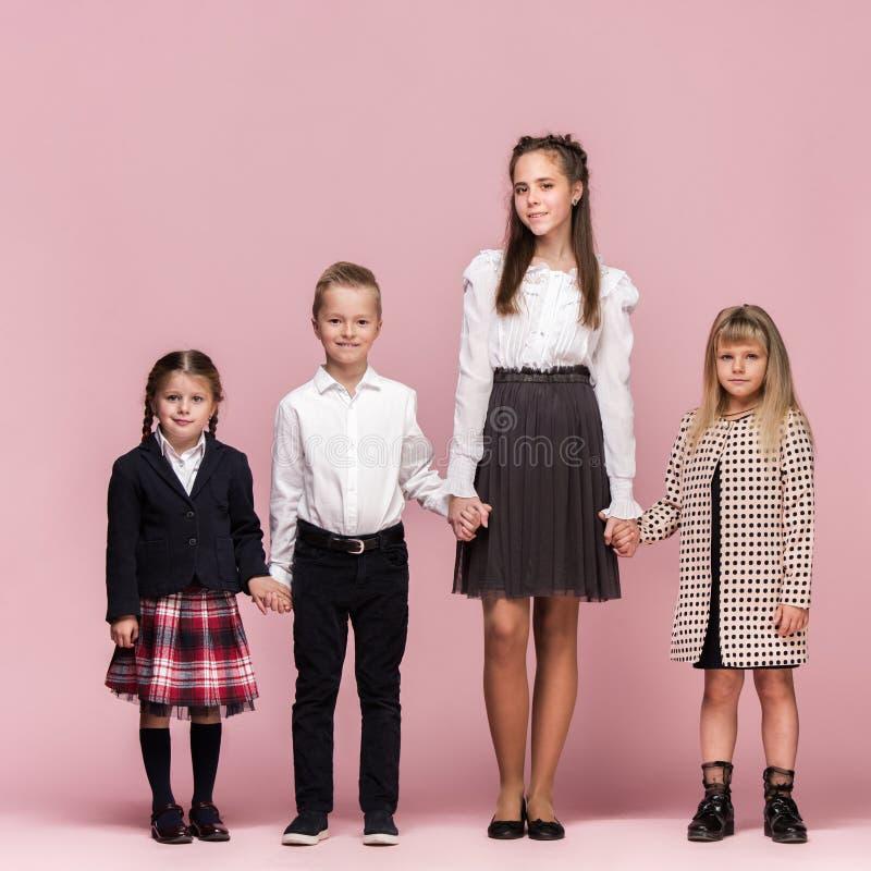 Leuke modieuze kinderen op roze studioachtergrond De mooie tienermeisjes en de jongen die zich verenigen stock afbeeldingen