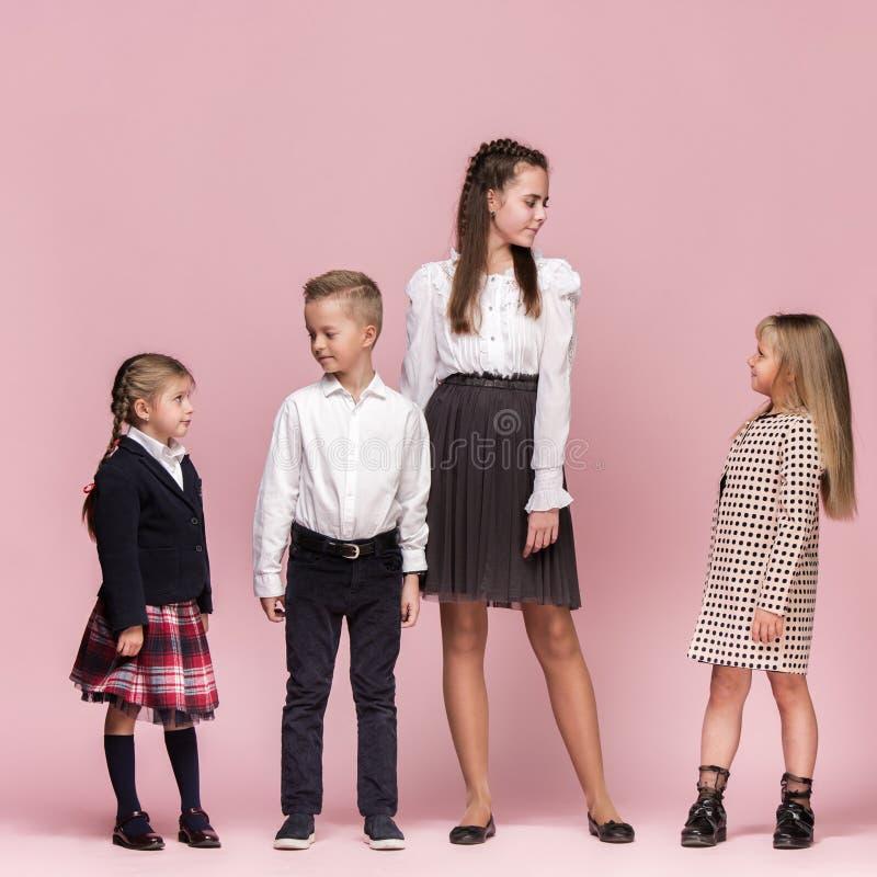 Leuke modieuze kinderen op roze studioachtergrond De mooie tienermeisjes en de jongen die zich verenigen royalty-vrije stock afbeelding