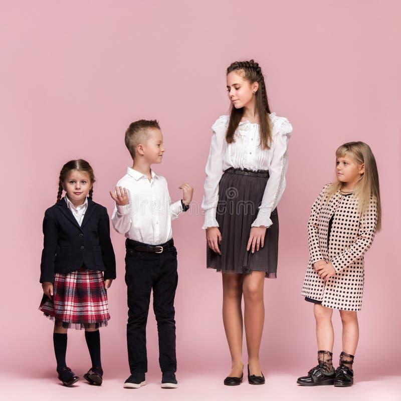 Leuke modieuze kinderen op roze studioachtergrond De mooie tienermeisjes en de jongen die zich verenigen royalty-vrije stock foto's