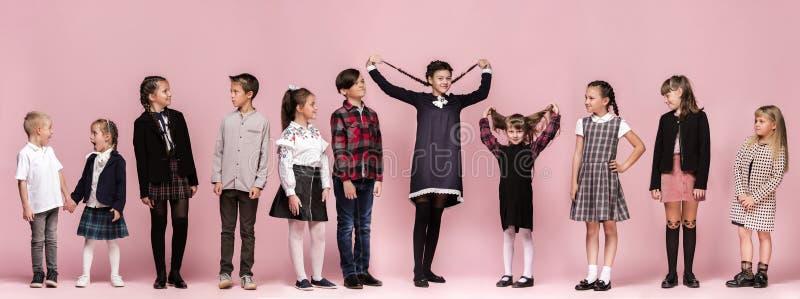 Leuke modieuze kinderen op roze studioachtergrond De mooie tienermeisjes en de jongen die zich verenigen royalty-vrije stock afbeeldingen
