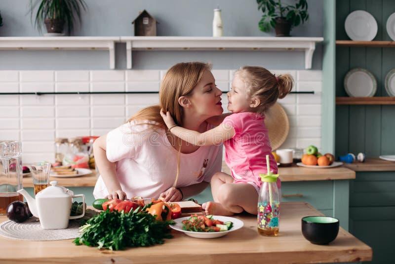 Leuke moeder en dochter die elkaar kussen bij keuken stock foto's