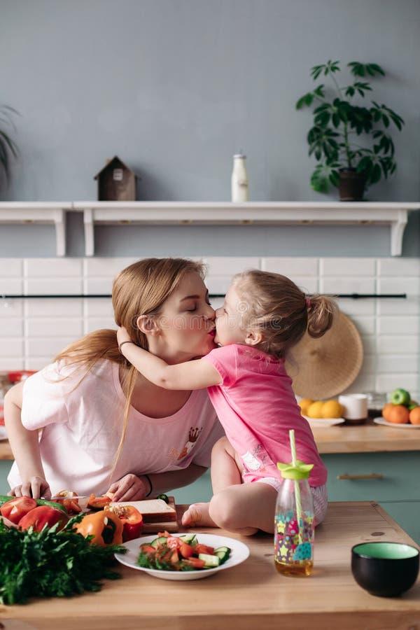 Leuke moeder en dochter die elkaar kussen bij keuken royalty-vrije stock fotografie