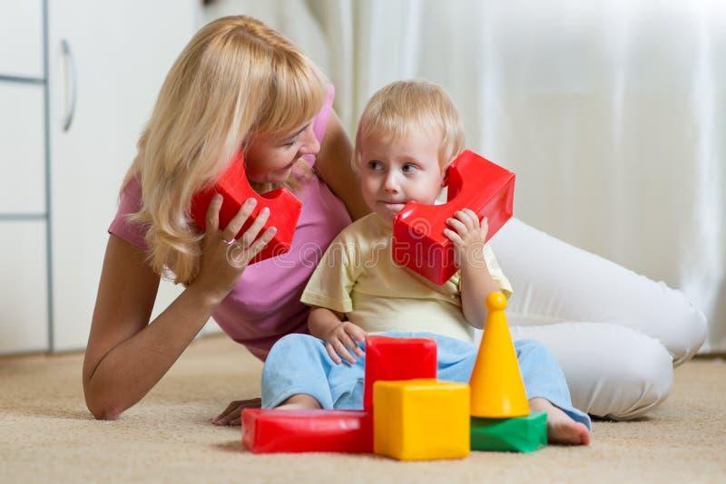 Leuke moeder en kindjongensrol die samen thuis spelen royalty-vrije stock foto's