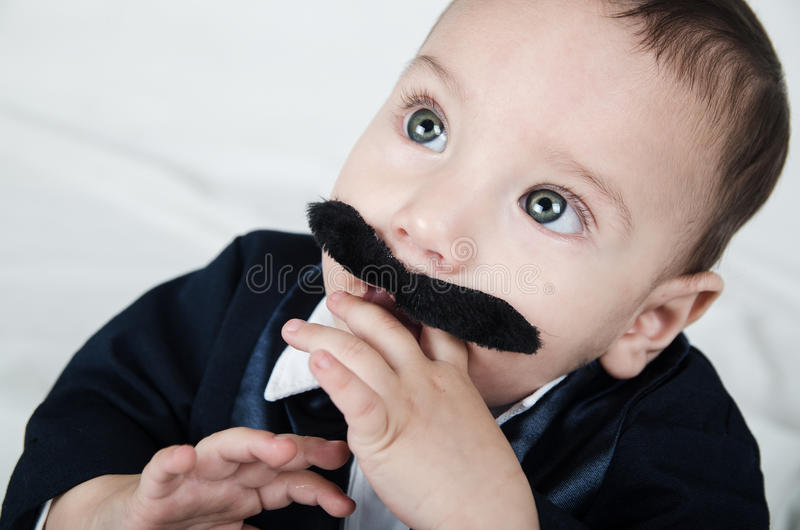 Leuke mooie babyjongen in kostuum met snor stock fotografie
