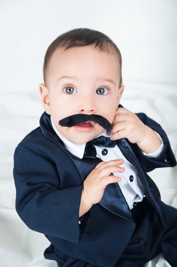 Leuke mooie die babyjongen in kostuum wordt verrast met royalty-vrije stock foto