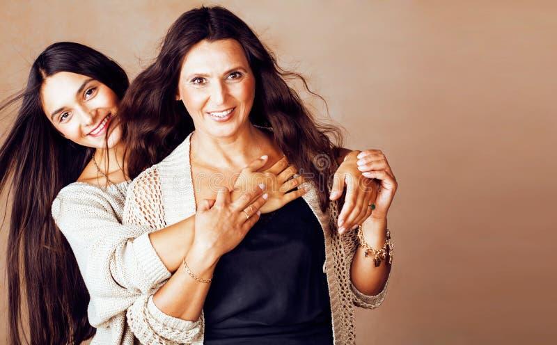 Leuke mooie tienerdochter met rijpe moeder die, manier st koesteren stock fotografie
