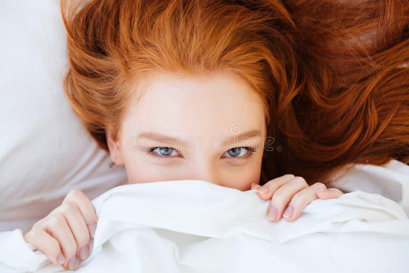 Leuke mooie vrouw met het rode haar verbergen onder witte deken royalty-vrije stock afbeeldingen