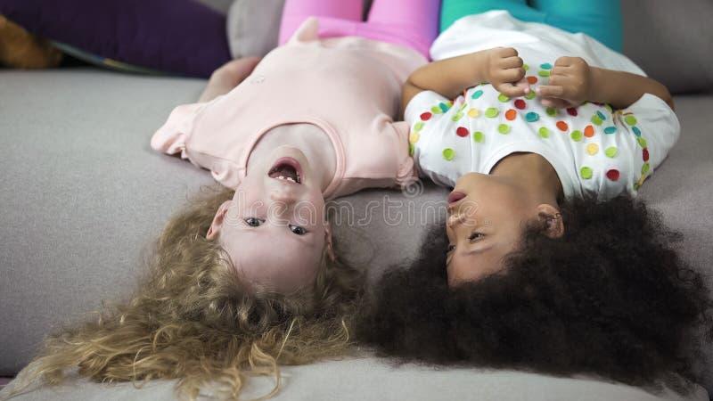 Leuke multi-etnische kinderen die op laag liggen en pret, kinderjaren en vakantie hebben stock foto