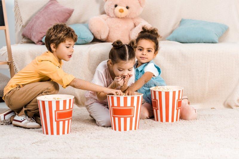 leuke multi-etnische kinderen die op tapijt zitten en royalty-vrije stock afbeeldingen