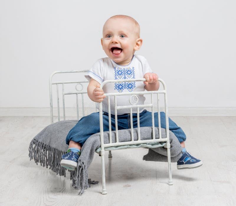 Leuke nieuwsgierige babyzitting op een klein bed royalty-vrije stock fotografie