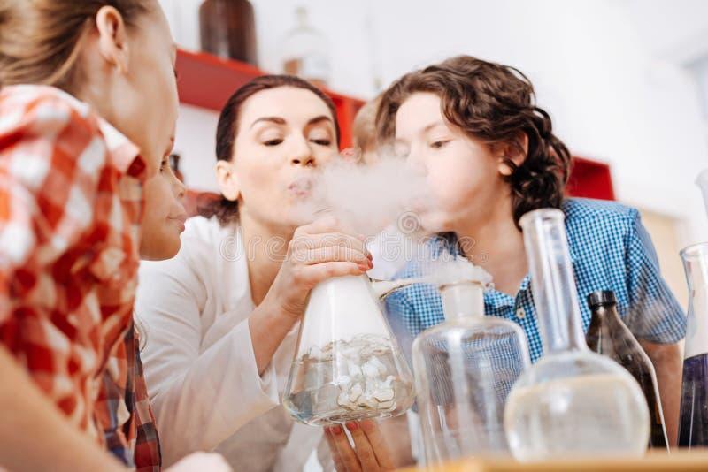 Leuke nieuwsgierige jongen die op de chemische fles blazen royalty-vrije stock fotografie