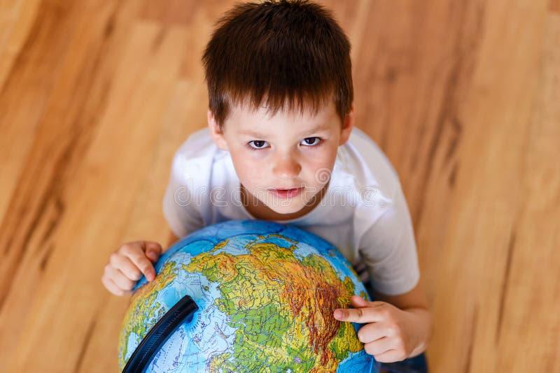 Leuke oud van vijf jaar toont continenten op een grote bol, hoogste mening stock fotografie
