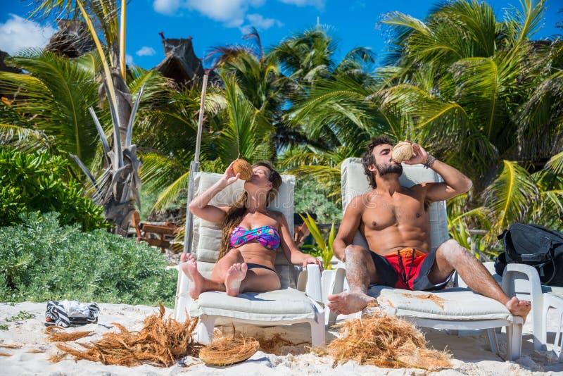 Leuke Paar het drinken Kokosnoot bij het Caraïbische strand van Tulum Riviera M royalty-vrije stock foto's