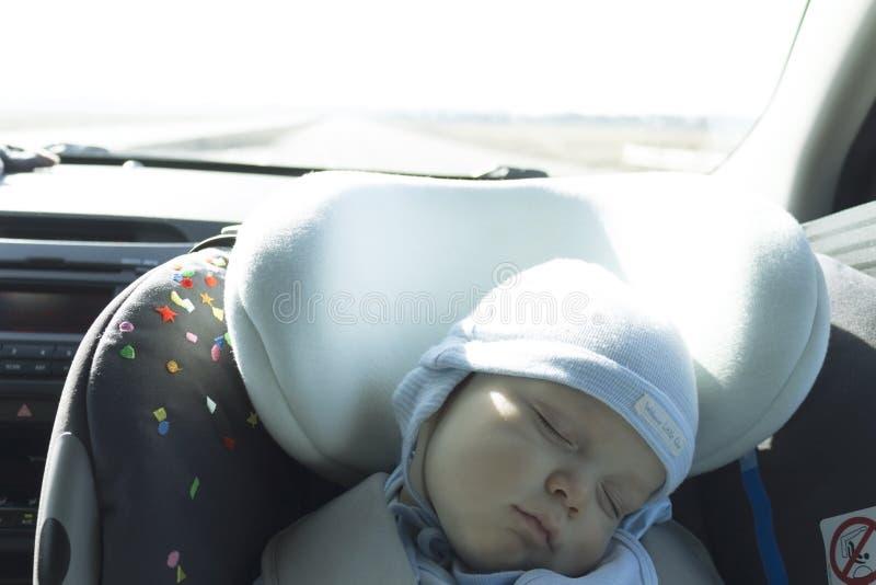 Leuke pasgeboren babyslaap in moderne autozetel Nieuw kind - geboren reizende veiligheid op de weg Veilige manier te reizen vastg royalty-vrije stock fotografie
