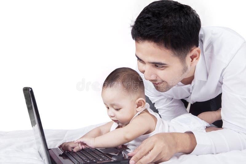 Leuke peuter het spelen laptop met zijn papa stock foto's