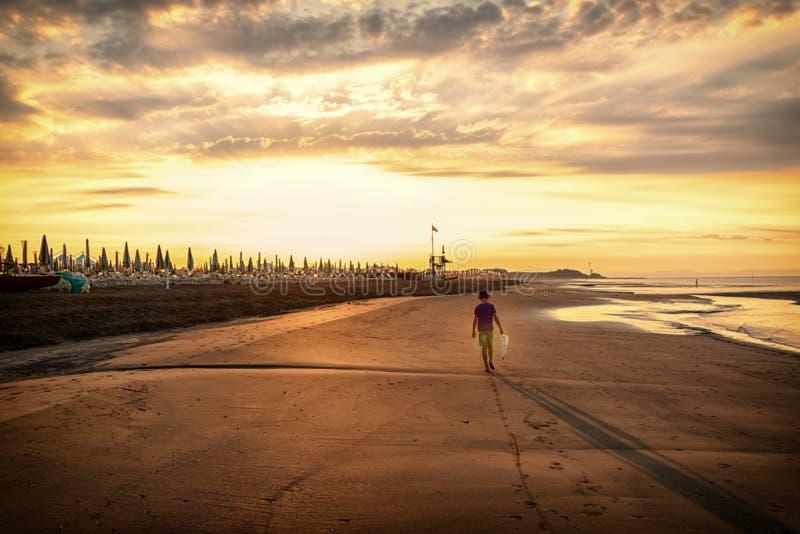 Leuke peuterjongen die alleen langs zandig strand, transparant water, landschapsachtergrond met ruimte voor tekst lopen, schoonhe stock fotografie