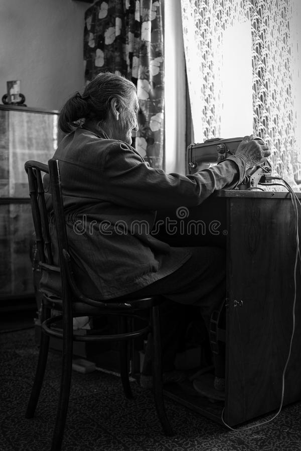Leuke 80 plus éénjarigen hogere vrouw die uitstekende naaimachine met behulp van Zwart-wit beeld van aanbiddelijke bejaarde naaie royalty-vrije stock foto