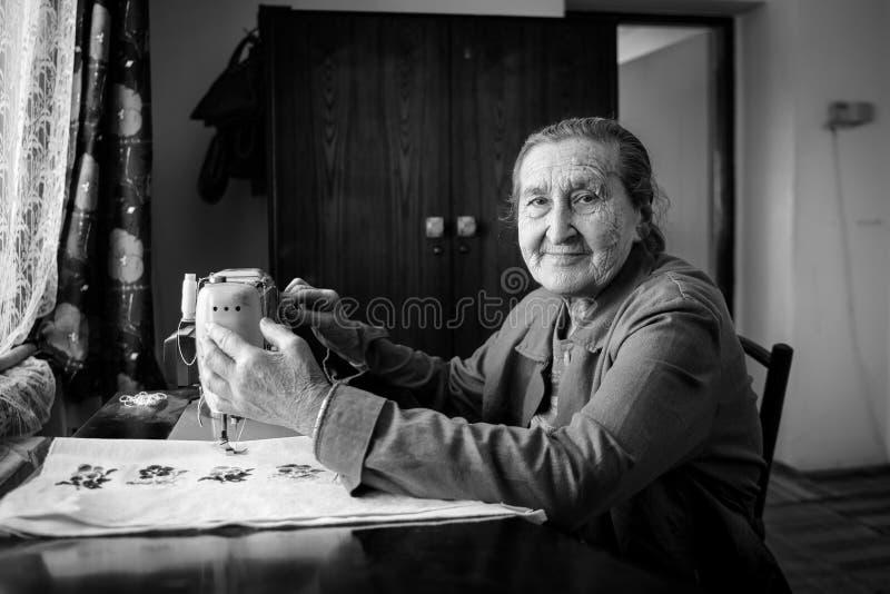 Leuke 80 plus éénjarigen hogere vrouw die uitstekende naaimachine met behulp van Zwart-wit beeld van aanbiddelijke bejaarde naaie stock foto