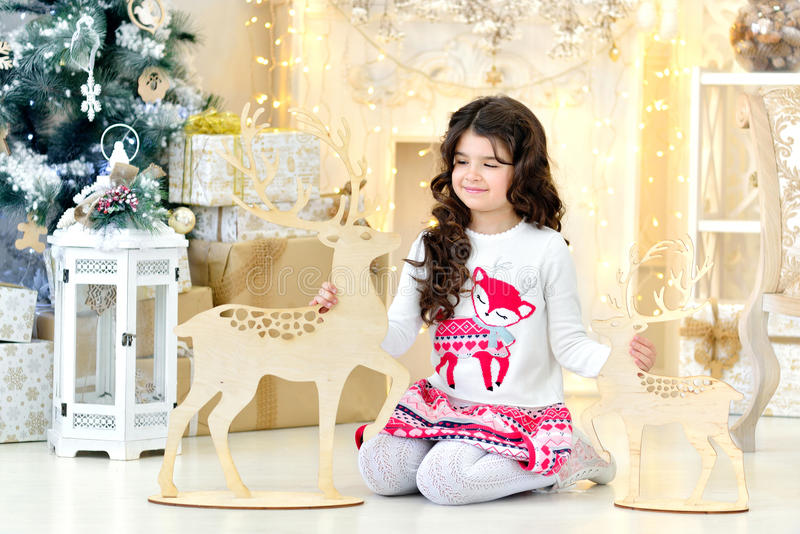 Leuke portraite van krullend meisje met de gouden magische lichten van Kerstmisslingers en boomdecoratie koestert stuk speelgoed  royalty-vrije stock afbeeldingen