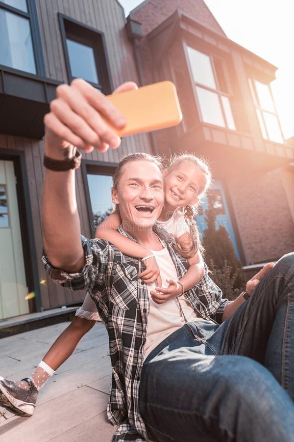 Leuke richtende dochter die haar vader koesteren terwijl het maken van foto met hem royalty-vrije stock foto