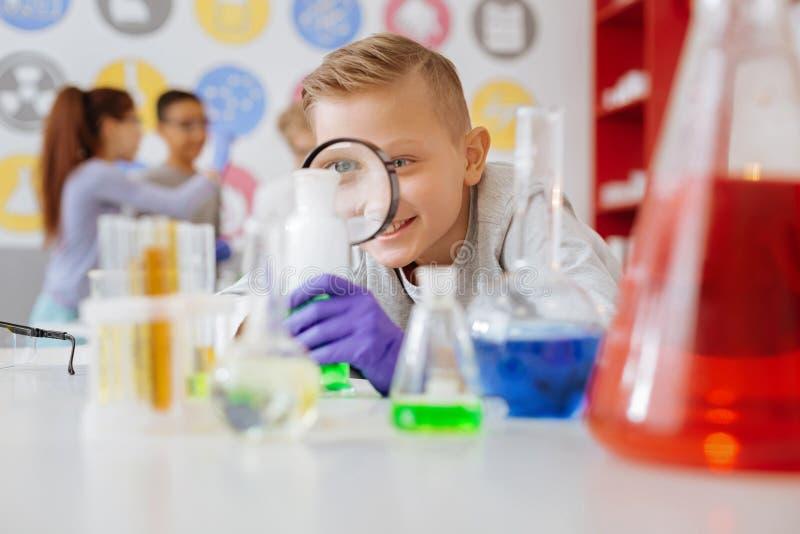 Leuke schooljongen die chemische reactie in laboratorium bestuderen royalty-vrije stock foto