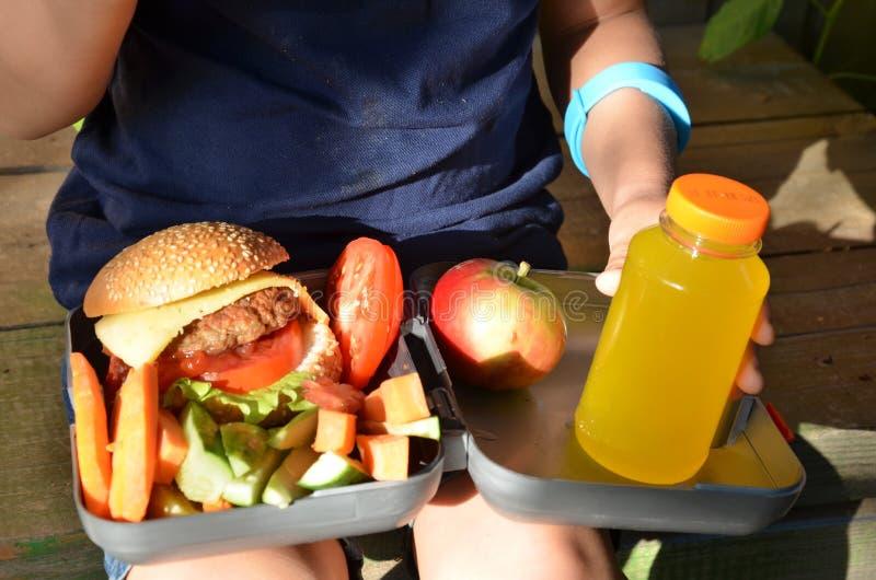 Leuke schooljongen die in openlucht de school van plasticklunch boxe eten Gezond schoolontbijt voor kind Voedsel voor lunch royalty-vrije stock afbeelding