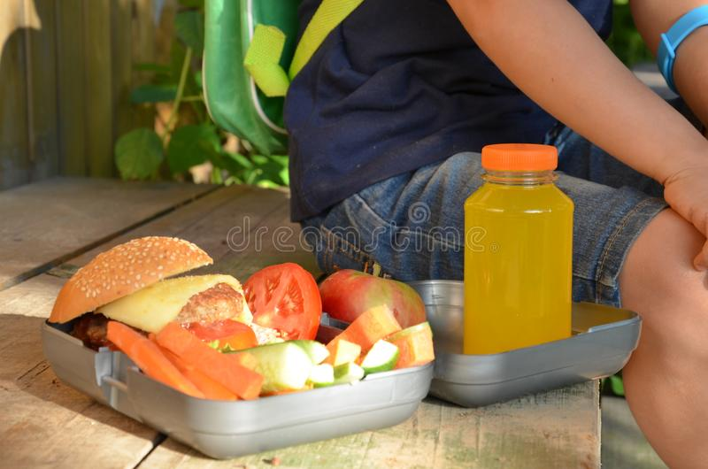 Leuke schooljongen die in openlucht de school van plasticklunch boxe eten Gezond schoolontbijt voor kind Voedsel voor lunch royalty-vrije stock foto