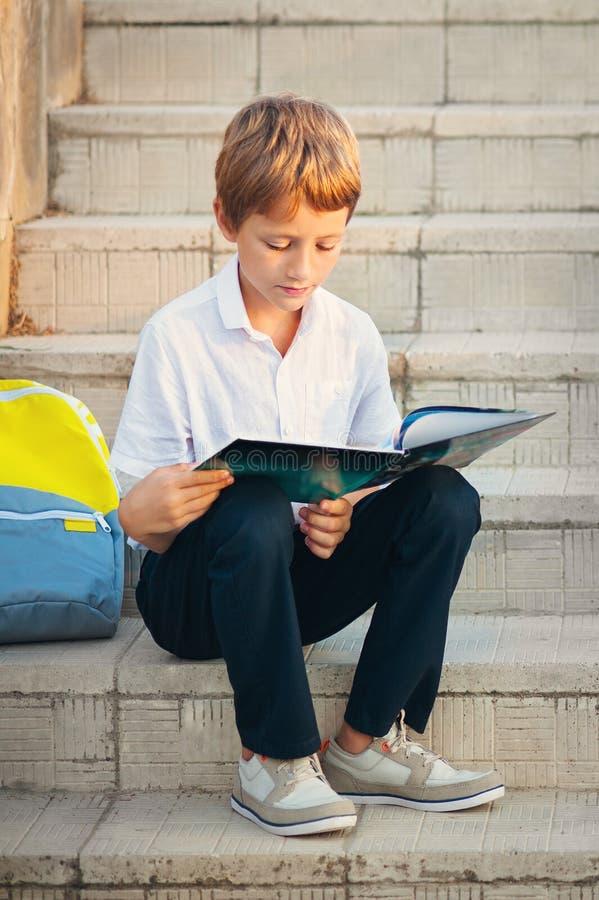 Leuke schooljongen die in openlucht op heldere de herfstdag bestuderen De jongen leest boek met rugzak Terug naar School Jonge st stock foto's