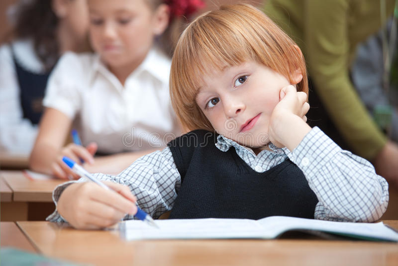 Leuke schooljongen in klaslokaal royalty-vrije stock afbeeldingen