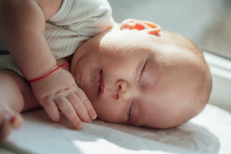 Leuke slaapbaby dichtbij het venster stock fotografie