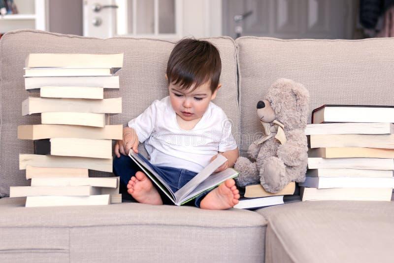 Leuke slim weinig babyjongen scherp over de zitting van het lezingsboek op bank met teddybeerstuk speelgoed en stapels van boeken stock fotografie