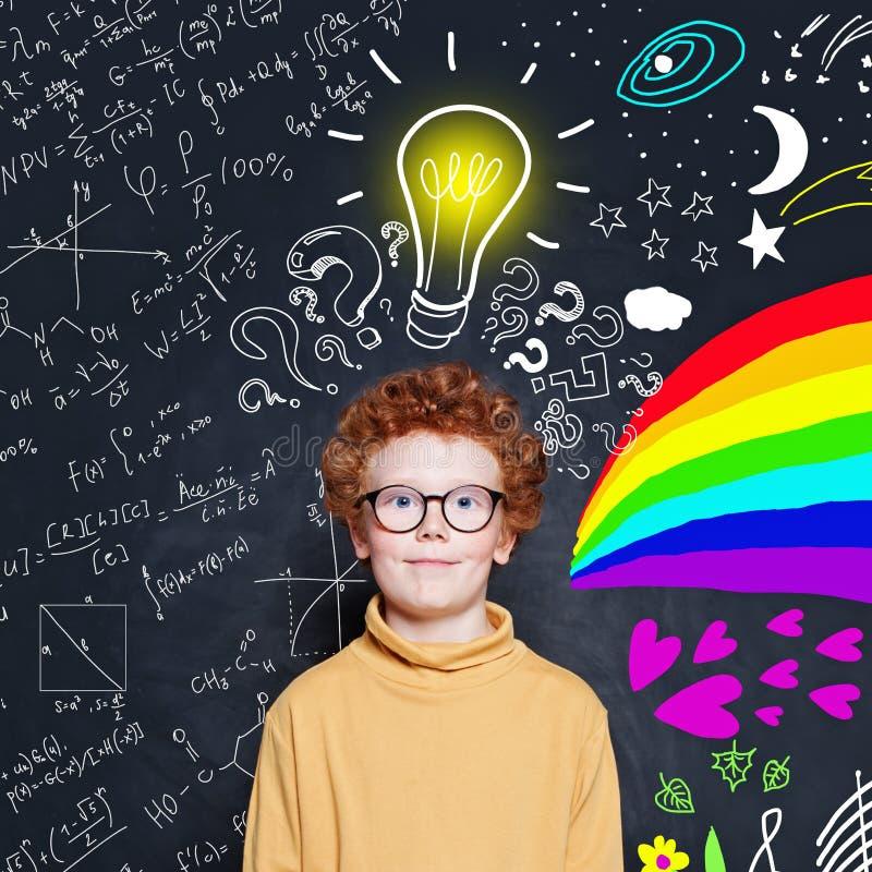 Leuke slimme jongen op bordachtergrond met idee lightbulb Wetenschap en kunstenmacht stock foto