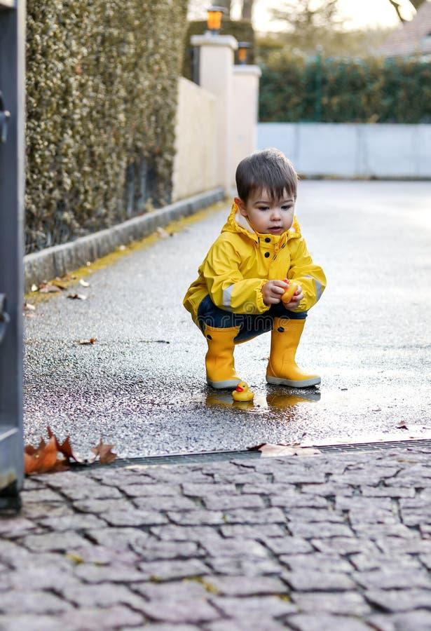 Leuke speels weinig babyjongen in heldere gele regenjas en rubberlaarzen die met rubbereenden in kleine vulklei bij de regenachti royalty-vrije stock afbeelding