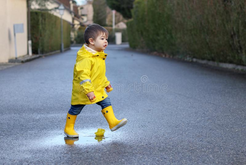 Leuke speels weinig babyjongen in heldere gele regenjas en rubberlaarzen met stuk speelgoed boot en rubbereenden die in kleine vu royalty-vrije stock afbeelding