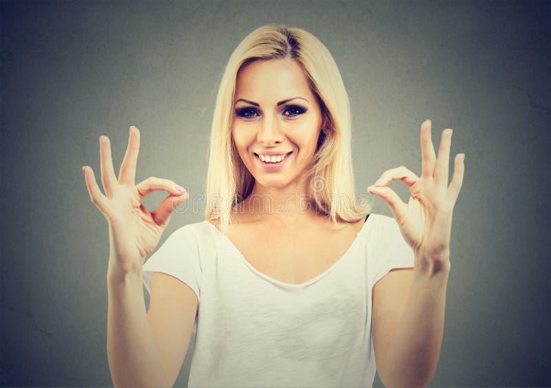 Leuke speelse blondevrouw die twee o.k. tekens tonen stock afbeelding