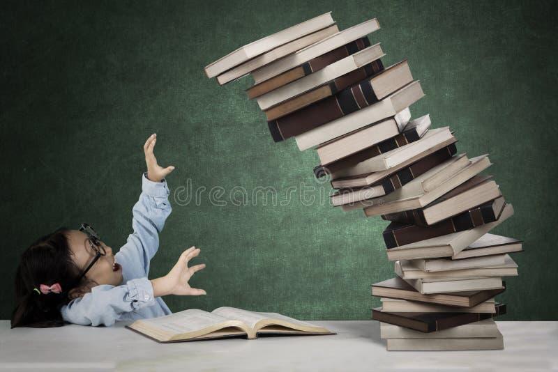 Leuke student met stapel van dalende boeken royalty-vrije stock fotografie