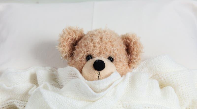 Leuke teddy behandeld met een warme deken, die in bed leggen stock foto's