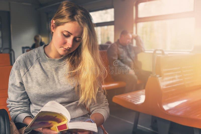 Leuke toeristenvrouw die een boek met rente lezen dichtbij het venster op de trein bij het warme stemmen stock afbeelding