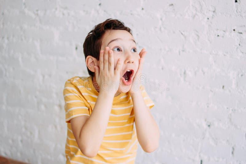 Leuke tween verraste jongen met grappig gezicht in gele die t-shirt op witte bakstenen muurachtergrond wordt geïsoleerd royalty-vrije stock afbeeldingen